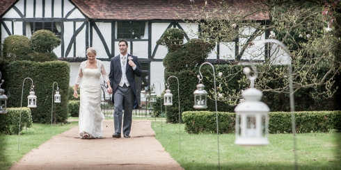 bride and groom walk towards the marquee